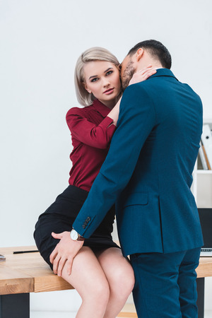 Photo for sexy young couple of business people kissing and flirting at workplace - Royalty Free Image