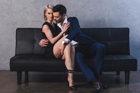 Foto de seductive young couple hugging in foreplay while sitting on couch - Imagen libre de derechos