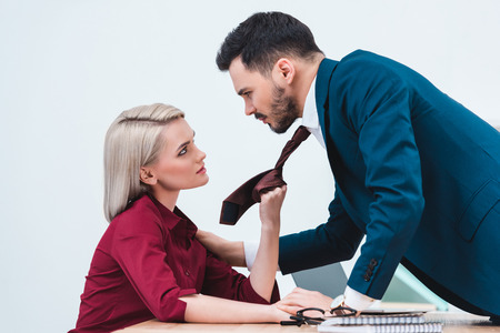 Photo pour side view of young businesswoman holding necktie of handsome businessman in office - image libre de droit
