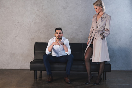 Photo pour sexy girl in coat and stockings flirting with handsome young businessman sitting on couch - image libre de droit