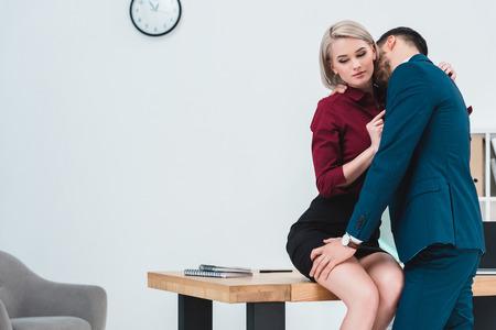 Photo pour seductive young couple of business people flirting in office - image libre de droit