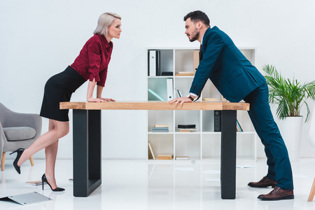 Photo pour side view of young business people leaning at table and looking at each other in office - image libre de droit