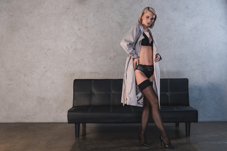 Photo for sexy young woman in lingerie, stockings and coat looking at camera - Royalty Free Image