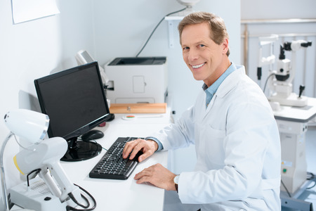 Foto de handsome smiling male ophthalmologist working with computer in clinic - Imagen libre de derechos