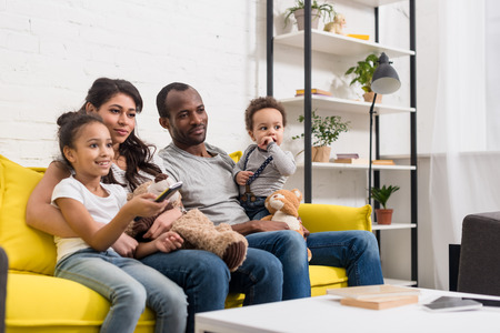 Photo pour young family watching tv together at living room - image libre de droit