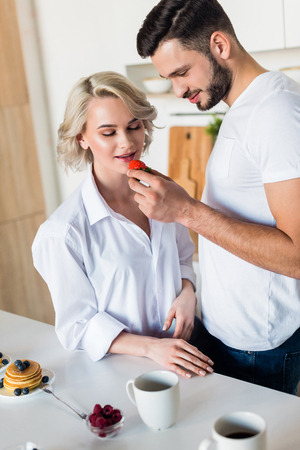 Photo pour smiling young man feeding sexy girlfriend with strawberry at morning - image libre de droit