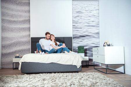 Photo pour Young male hugging his girlfriend in bedroom with design interior - image libre de droit