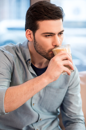 Photo pour portrait of young handsome man drinking ice coffee in cafe - image libre de droit