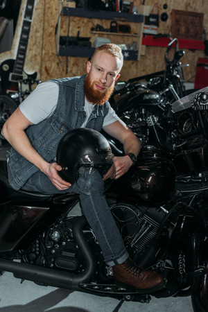 Foto de young man sitting on motorbike with helmet at garage - Imagen libre de derechos
