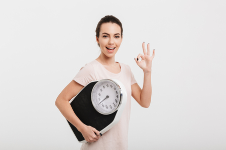 Foto de beautiful girl holding scales and showing ok gesture isolated on white - Imagen libre de derechos