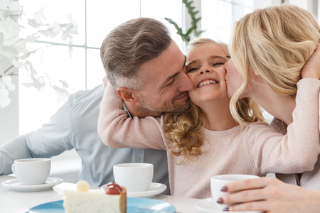 Photo pour parens kissing their daughter while spending time in cafe together - image libre de droit