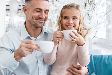Photo pour young father and daughter drinking tea in cafe - image libre de droit
