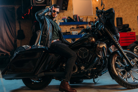 Foto de handsome young man in sunglasses sitting on bike at garage - Imagen libre de derechos