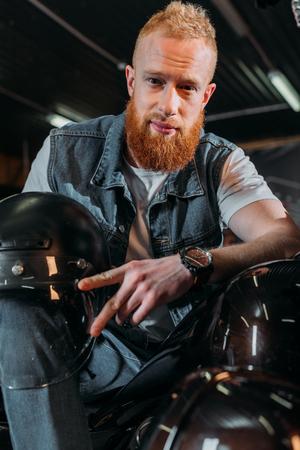 Foto de handsome young man sitting on bike with helmet at garage - Imagen libre de derechos