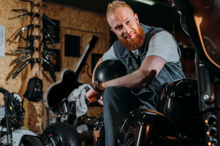 Foto de bearded young man sitting on bike with helmet at garage - Imagen libre de derechos
