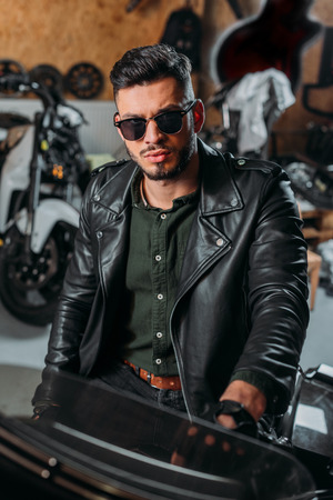Foto de handsome rockabilly man sitting on bike at garage - Imagen libre de derechos