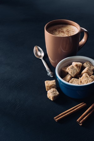Photo pour close up view of cup of coffee, bowl with brown sugar and cinnamon sticks on dark surface - image libre de droit