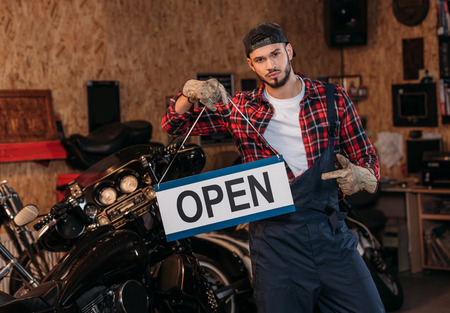 Photo for handsome bike repair station worker pointing at open signboard at garage - Royalty Free Image
