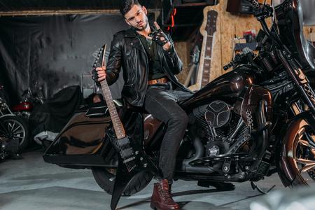 Foto de stylish young man in leather jacket sitting on bike with electric guitar at garage - Imagen libre de derechos