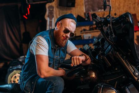 Foto de young man looking at watch while sitting on bike at garage - Imagen libre de derechos