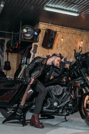 Foto de handsome young man sitting on bike with electric guitar at garage - Imagen libre de derechos
