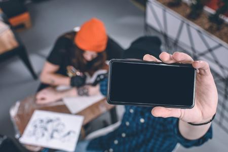 Foto de Phone in male hands in front of tattooing process in studio - Imagen libre de derechos
