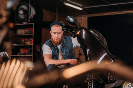 Foto de portrait of handsome young man on bike at garage - Imagen libre de derechos