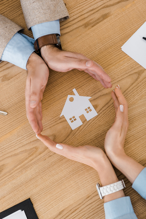 Photo for Couple making circle with hands on wooden table with paper house inside, house insurance - Royalty Free Image