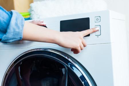 Photo pour close-up partial view of woman using washing machine at home - image libre de droit