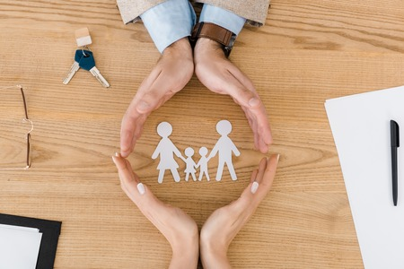 Photo for Couple making circle with hands on wooden table with paper people inside, family insurance - Royalty Free Image