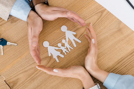 Photo for couple making circle with hands on wooden table with paper people inside - Royalty Free Image