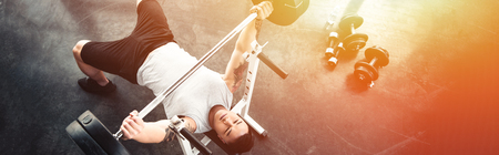 Foto de Muscular sportsman exercising with barbell at gym in sunlight - Imagen libre de derechos