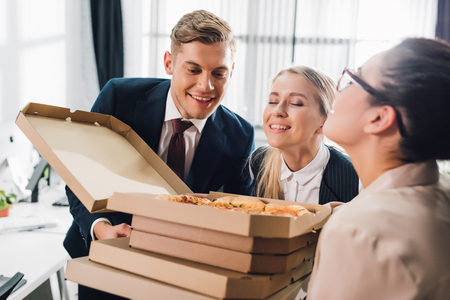Photo for Happy young business colleagues smelling tasty pizza in office - Royalty Free Image