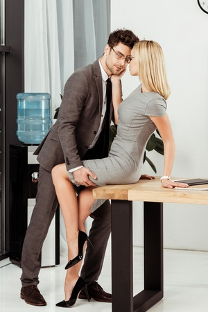 Foto de side view of young business colleagues flirting at workplace in office, offirce romance concept - Imagen libre de derechos