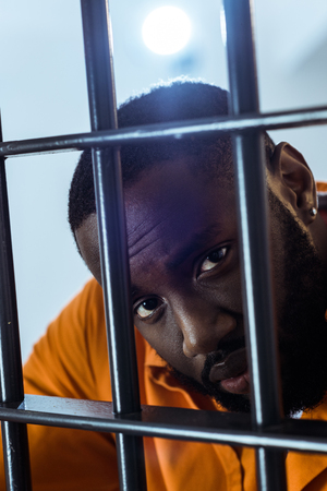 Photo for african american prisoner looking at camera behind prison bars - Royalty Free Image