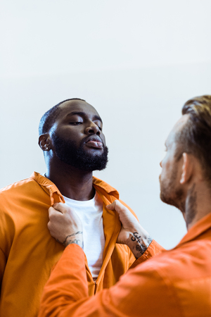 Foto de prisoner threatening african american cellmate isolated on white - Imagen libre de derechos