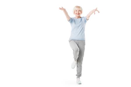 Photo pour Senior sportswoman standing on one leg isolated on white - image libre de droit
