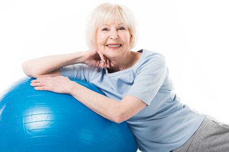 Photo pour Portrait of smiling senior sportswoman with fitness ball isolated on white - image libre de droit