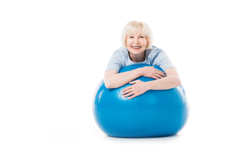Foto de Portrait of smiling senior sportswoman with fitness ball isolated on white - Imagen libre de derechos