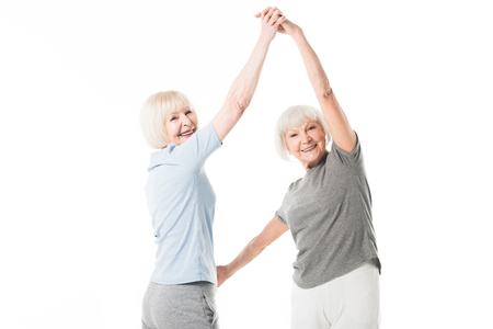 Foto de Two smiling senior sportswomen doing exercise isolated on white - Imagen libre de derechos