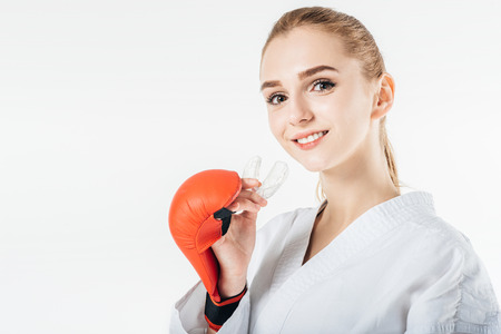 Photo pour smiling female karate fighter holding mouthguard isolated on white - image libre de droit