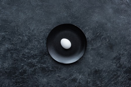 Photo for White egg on black plate on dark background - Royalty Free Image