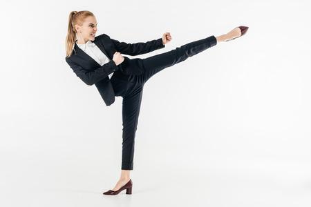 Foto de businesswoman performing karate kick in suit and high heels isolated on white - Imagen libre de derechos
