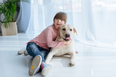 Foto de Child with down syndrome embracing Labrador retriever lying on the floor - Imagen libre de derechos