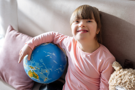 Foto de Smiling child with down syndrome holding globe - Imagen libre de derechos