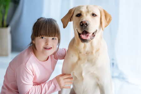 Foto de Happy child girl with down syndrome cherishing Labrador retriever - Imagen libre de derechos