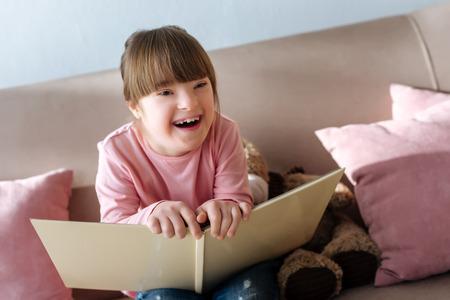 Foto de Kid with down syndrome holding book and laughing - Imagen libre de derechos