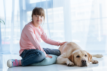 Foto de Child with down syndrome sitting on the floor with Labrador retriever - Imagen libre de derechos