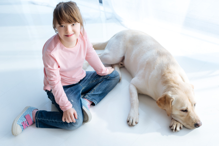 Foto de Top view of child with down syndrome and dog retriever in room - Imagen libre de derechos