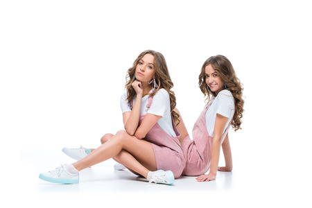 Photo pour beautiful serious and smiling young twins sitting and looking at camera on white - image libre de droit